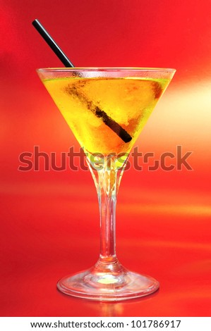 a glass with a yellow cocktail on a red background - stock photo