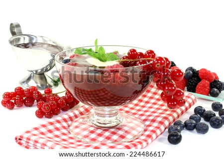 a glass with red fruit jelly, vanilla sauce and mint - stock photo