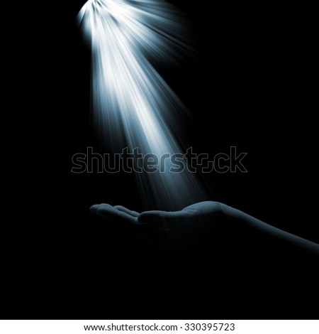 A glimmer of hope flowing down to the hand of the woman on a dark background. The light of faith - stock photo