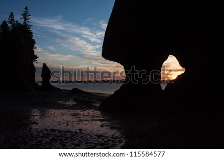 A glimpse of the sun slowly rising, seen through an opening of one of the Famous Hopewell Rocks flowerpot formations. New Brunswick, Canada. - stock photo