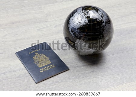 A globe next to a passport on a wood floor - stock photo