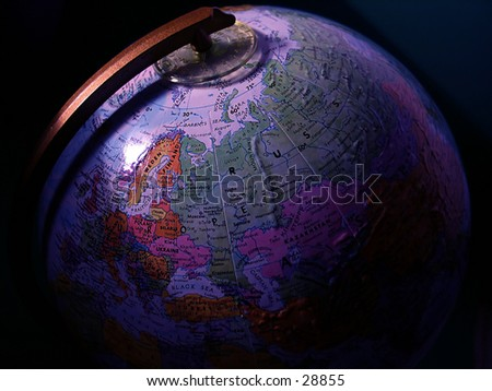 A globe with light cast on its surface, dark shadows. - stock photo