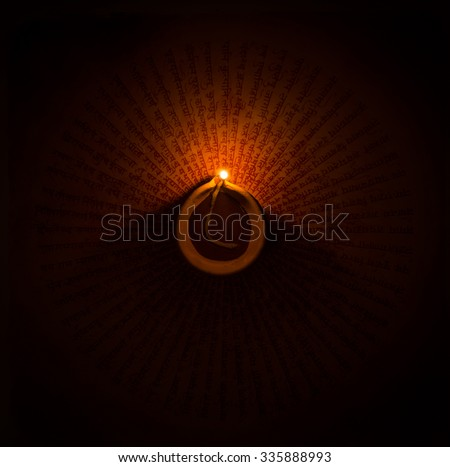 A glowing earthen ghee lamp in the dark. Handwritten mantra visible at the background. - stock photo