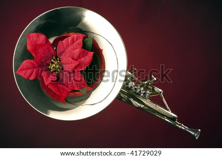 A gold brass French horn and red poinsettia flower isolated  against a spotlight red background. - stock photo