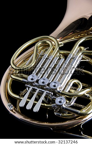 A gold brass French Horn isolated against a black background in the vertical format with copy space. - stock photo