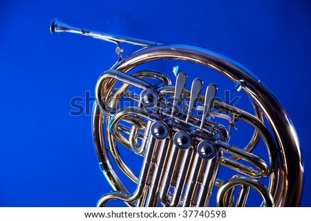 A gold brass French horn isolated against a blue background in the horizontal format with copy space. - stock photo