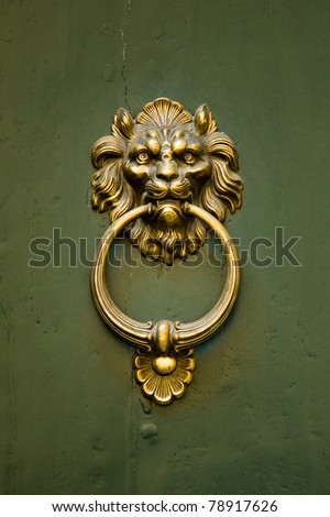 A gold doorknocker in the shape of a ferocious lion is mounted on a green door - stock photo