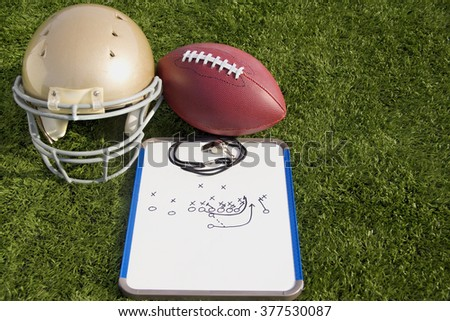 A gold helmet, football and clipboard on a field. - stock photo