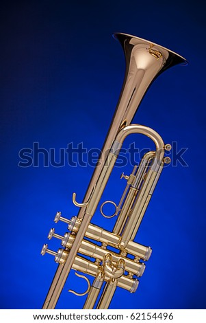 A gold professional trumpet isolated against a spotlight blue background with copy space. - stock photo