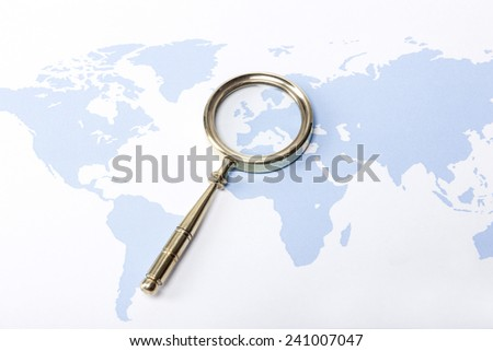 A gold vintage(classic, old) magnifier(reading glass) focus in europe on the blue world map. - stock photo