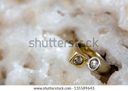 A gold/white gold ring inlaid with diamonds resting on a rock made of clusters of salt crystals. Shot on the beach of the infamously salty Dead Sea in Israel. - stock photo