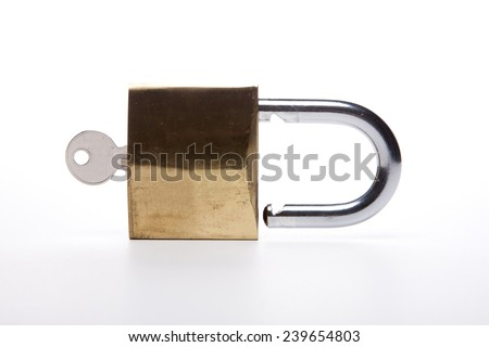 A gold(yellow) padlock(combination lock, bicycle lock) locked with key isolated white at the studio.  - stock photo