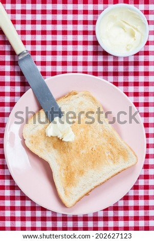 A golden brown slice of toast on a pink plate with butter ready to be spread - stock photo