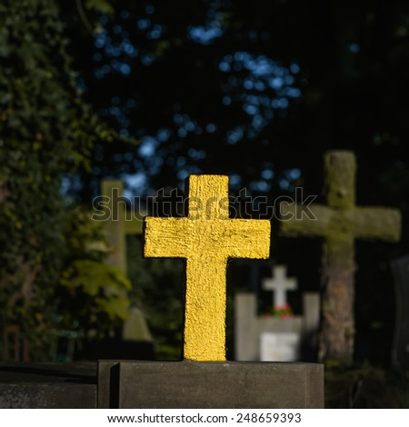 a golden cross on the graveyard - stock photo