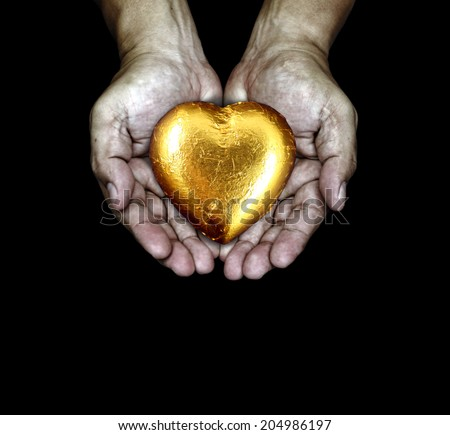 A golden heart in the care of a pair of rugged hand.  - stock photo
