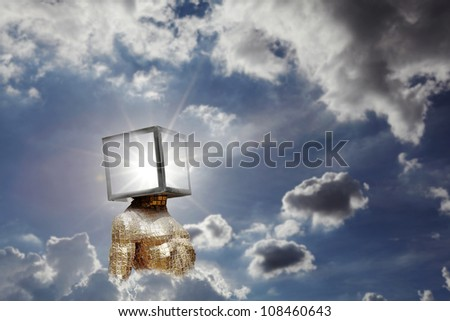 A golden humanoid with a shinning star radiating in its head on a dramatic blue cloudy sky for the concept of human intervention with nature. - stock photo