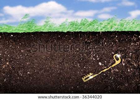a golden key hidden under the ground - stock photo