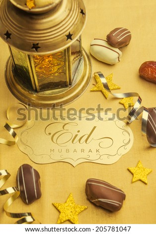 A golden plaque with 'Eid Mubarak' message. A set up with arabic lantern and date chocolates - stock photo