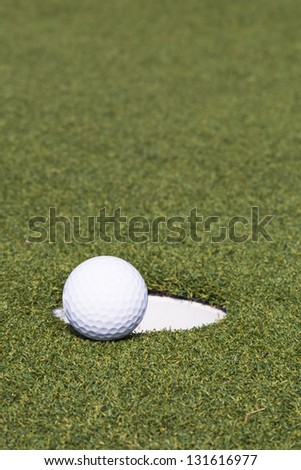 A golf ball and hole - stock photo