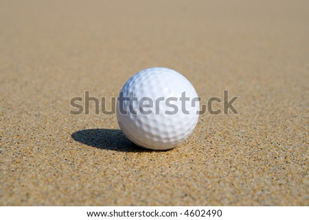 A golf ball in the sand with shallow focus. - stock photo