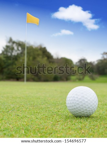 A golf ball on a green with the flag in the background - stock photo