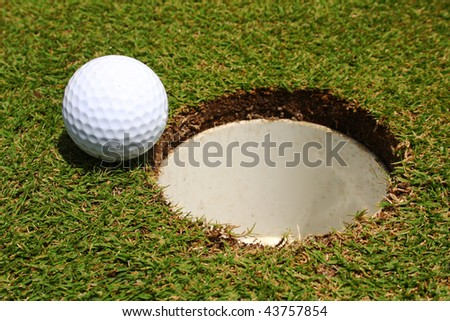 A golf ball on the edge of a hole - stock photo