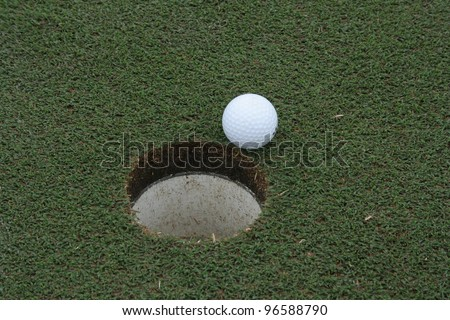 a golf ball on the edge of the cup - stock photo