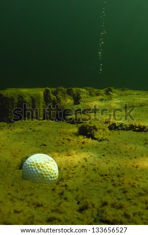 A golf ball rests in a water hazard after a poor shot. - stock photo