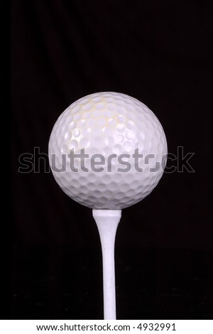 A golf ball rests on a tee. Black background. - stock photo