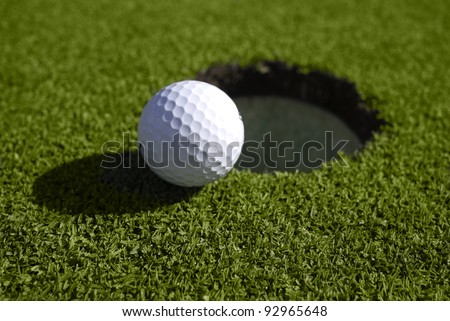 A golf ball sits at the lip of the hole on the putting green. - stock photo