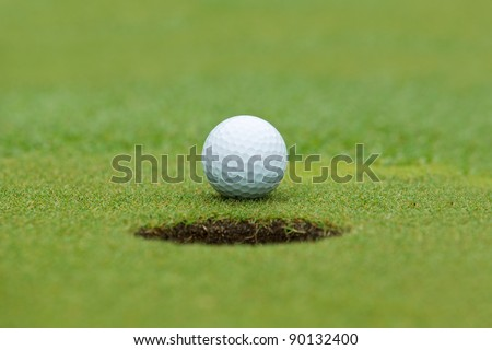 A golf ball sitting behind a hole - stock photo