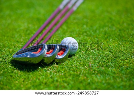 A golf balls rests on the tee grass with irons Selective focus with plenty of copy space. - stock photo