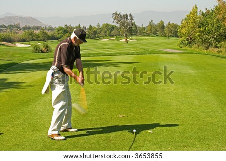 A golf course and senior golfers in action - stock photo