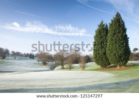 A golf course drapped in winter frost in the UK. - stock photo
