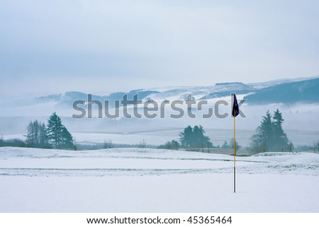 A golf course in Scotland on a snowy winter morning in December. View from a green with a blue flag, with trees, mist and mountains in the background. - stock photo