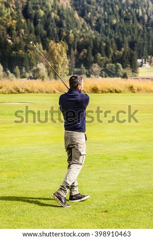 a golf player making a swing on a vibrant beautiful golf course - stock photo
