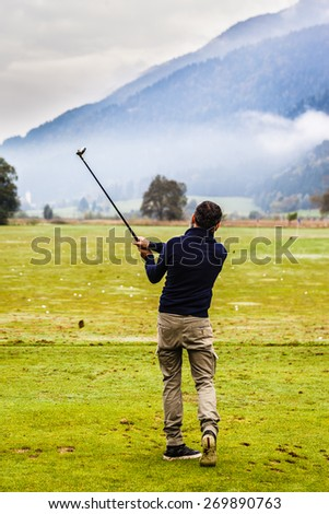 a golf player practicing the swing on the driving range - stock photo