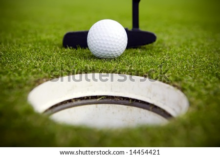 A golfer attempts to make a very short putt - stock photo