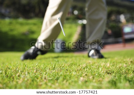 A golfer in action on a practice range, hitting the ball with a club. Shot taken a split-second after impact with the tee still airborne after being hit by the club. - stock photo