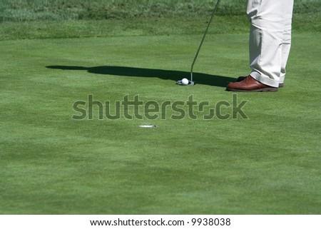 A golfer preparing to attempt a putt - stock photo