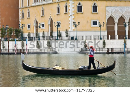 A gondalier waves as he negotiates the lake at the venetian in macau - stock photo