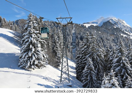 A gondola transports skiers and snowboarders up a mountain above a forest of trees in a luxurious ski resort in the Swiss Alps, Gryon, Switzerland. - stock photo