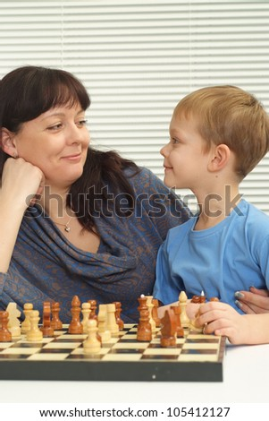 A good Caucasian mother and son playing chess against a light background - stock photo