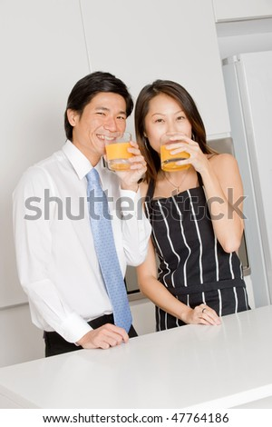 A good looking couple drinking orange juice at home - stock photo