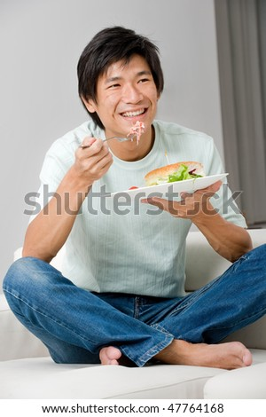 A good looking man having a sandwich on his couch at home - stock photo