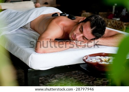 A good-looking man relaxing with hot stones on back before massage - stock photo