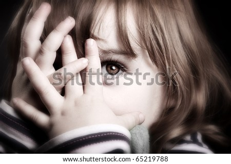 A gorgeous little girl playing peekaboo and peering through her fingers. Adorable. - stock photo