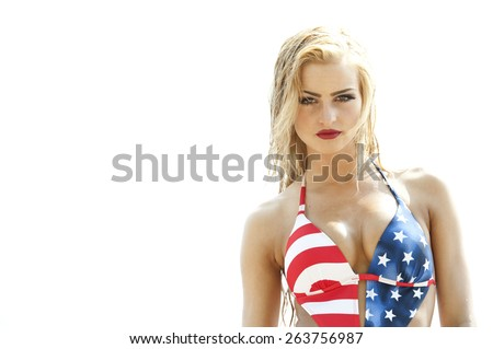 A gorgeous young fit and petite blonde with wet hair looking at the camera while wearing an American flag one piece swimsuit to celebrate 4th of July at the beach on a sunny day. - stock photo