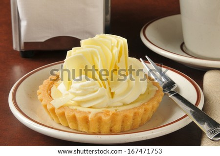 A gourmet key lime dessert tart with a cup of coffee - stock photo