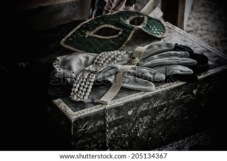 A grainy desaturated fine art still life image of woman's various theater props and costume parts. - stock photo